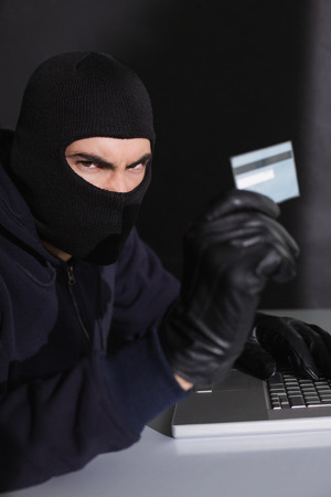 Angry hacker using credit card and laptop on black background photo