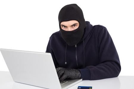 entering information: Hacker in balaclava hacking a laptop on white background