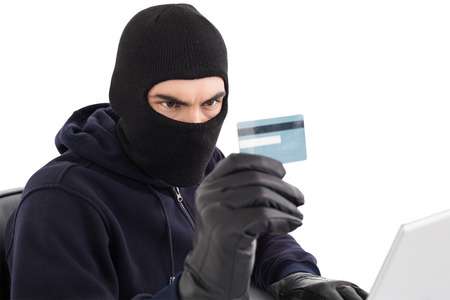 Burglar using credit card and laptop on white background photo