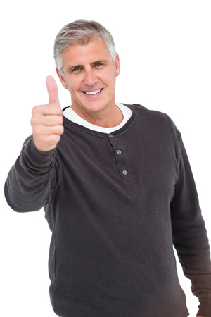 thumbs up gesture: Casual man showing thubms up at camera on white background
