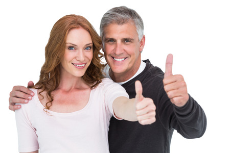 thumbs up gesture: Casual couple showing thumbs up on white background