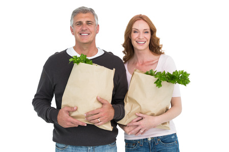 Casual couple holding grocery bags on white background photo