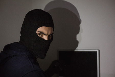 Hacker in balaclava hacking laptop while looking at camera in house photo