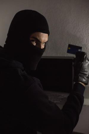 Hacker using debit card and laptop in house photo