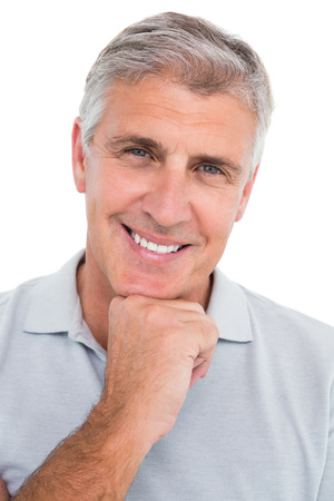 Casual man smiling with hand on chin on white background photo