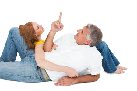 Casual couple lying on floor on white background