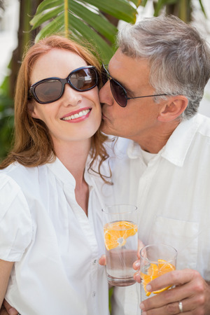 holidaying: Holidaying couple toasting with cocktails in a green park Stock Photo