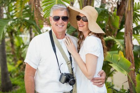 holidaying: Holidaying couple smiling at camera in a green park