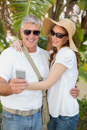 holidaying: Holidaying couple taking a selfie in a green park