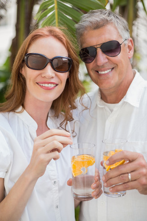 Holidaying couple toasting with cocktails in a green park photo