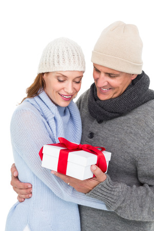 warm clothing: Casual couple in warm clothing holding gift on white background