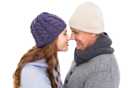 facing each other: Couple in warm clothing facing each other on white background Stock Photo