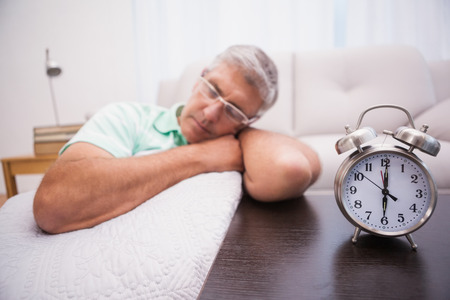 dozing: Man dozing on the couch beside alarm clock at home in the living room Stock Photo