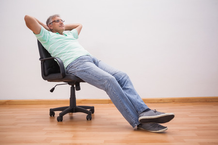 Mature man leaning back in swivel chair at home in the living room Stock Photo