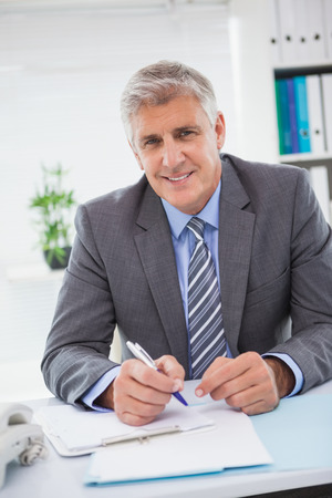 hombre escribiendo: Sonriente hombre de negocios escrito en el portapapeles en su oficina