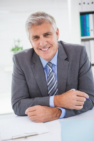 businessman smiling: Smiling businessman at his desk in his office