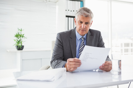 office attire: Mature businessman looking at document in his office Stock Photo