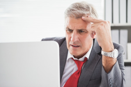 confused man: Confused businessman looking at his laptop in his office