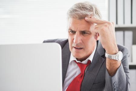 Verward zakenman die zijn laptop in zijn kantoor Stockfoto