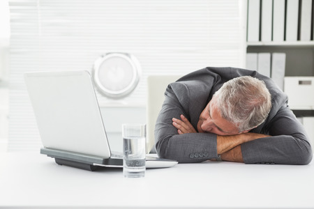 tired businessman: Mature businessman sleeping on desk in his office