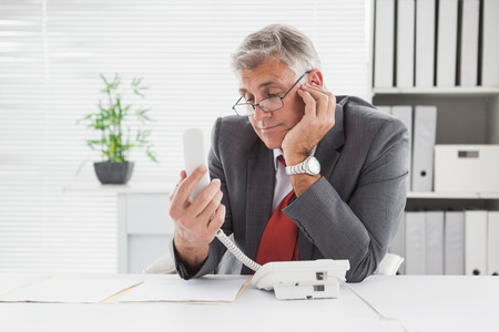 businessman waiting call: Smiling businessman put on hold in his office