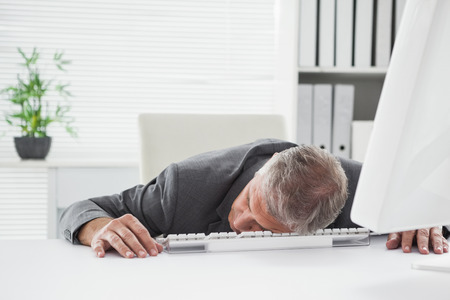 sleeping at desk: Exhausted businessman sleeping at his desk in his office Stock Photo