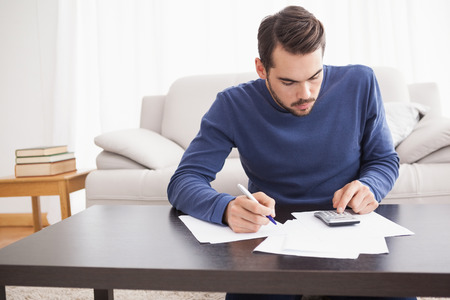 figuring: Young man paying his bills at home in the living room Stock Photo