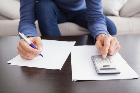 young adult men: Young man paying his bills at home in the living room Stock Photo
