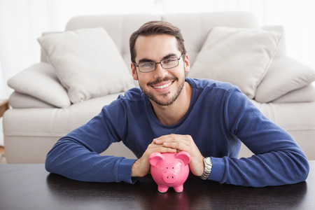 man holding money: Smiling young man with piggy bank at home in the living room