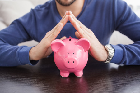 young adult men: Young man with piggy bank at home in the living room Stock Photo