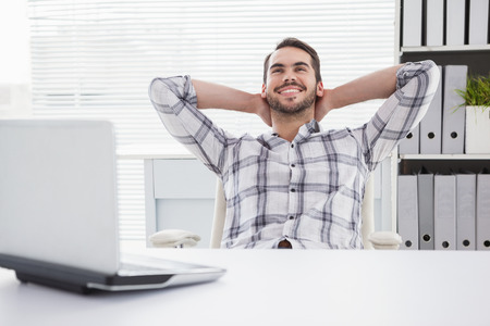 Casual businessman relaxing at desk leaning back in his office Banque d'images