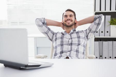 ejecutivos: Hombre de negocios ocasional que se relaja en el escritorio recost�ndose en su oficina