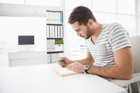serious business: Casual businessman highlighting a book in his office Stock Photo