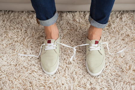 tied together: Casual mans shoelaces tied together at home in the living room