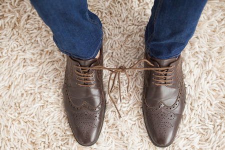 brogues: Classy mans shoelaces tied together  at home in the living room Stock Photo