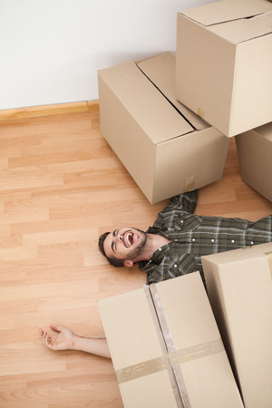 household accident: Man lying under fallen boxes at home in the living room