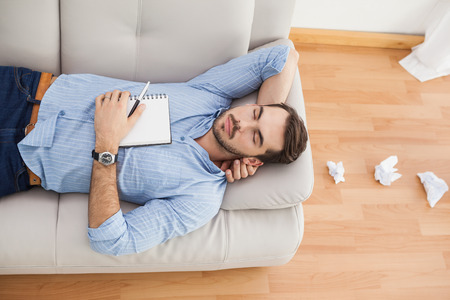 writer's block: Casual man lying on couch with crumpled papers at home in the living room