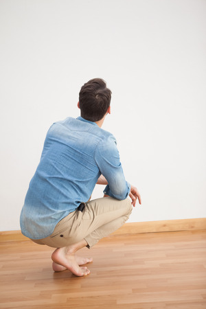 barefoot man: Casual man crouching on floor looking at wall at home in the living room