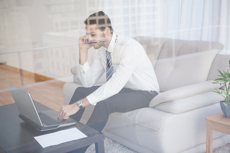 Businessman working on his couch seen through glass at home in the living room photo