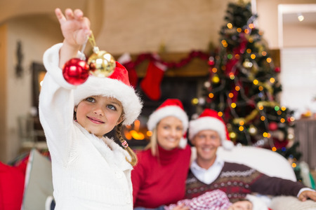 wearing santa hat: Cute little girl wearing santa hat holding bauble at home in the living room