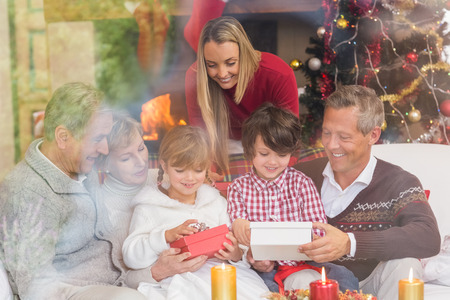 family sofa: Multi generation family opening presents on sofa at home in the living room Stock Photo