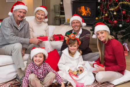 Happy family at christmas holding gifts at home in the living room photo