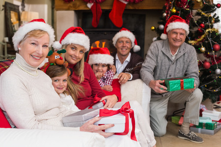 Portrait of a happy extended family in santa hat holding gifts at home in the living room photo