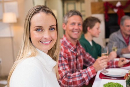 Woman smiling at camera during christmas dinner at home in the living room photo