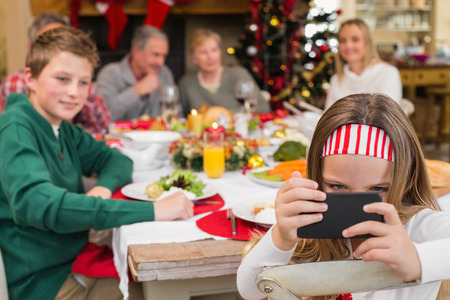 Little girl holding smartphone during christmas dinner at home in the living room photo