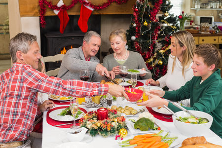Three generation family having christmas dinner together at home in the living room Stock Photo