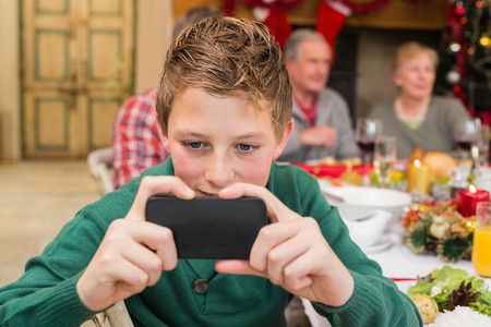 lady on phone: Young boy holding smartphone during christmas dinner at home in the living room Stock Photo