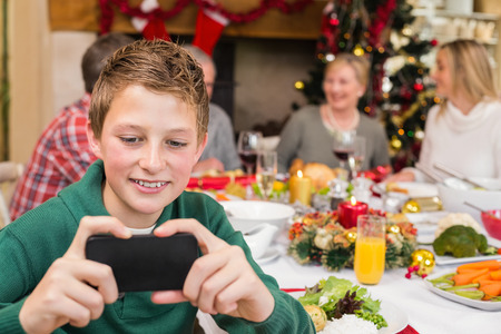 Young boy holding smartphone during christmas dinner at home in the living room photo