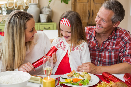 Little girl pulling a christmas cracker with their parents at home in the living room photo