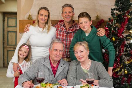 convivencia familiar: familia extensa feliz mirando a la cámara en tiempo de Navidad en casa en la sala de estar